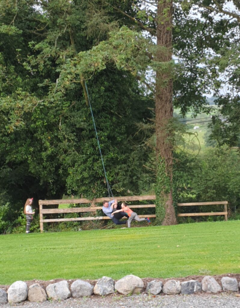 Gerry Caoimhe and Caolán on the tyre swing in their garden