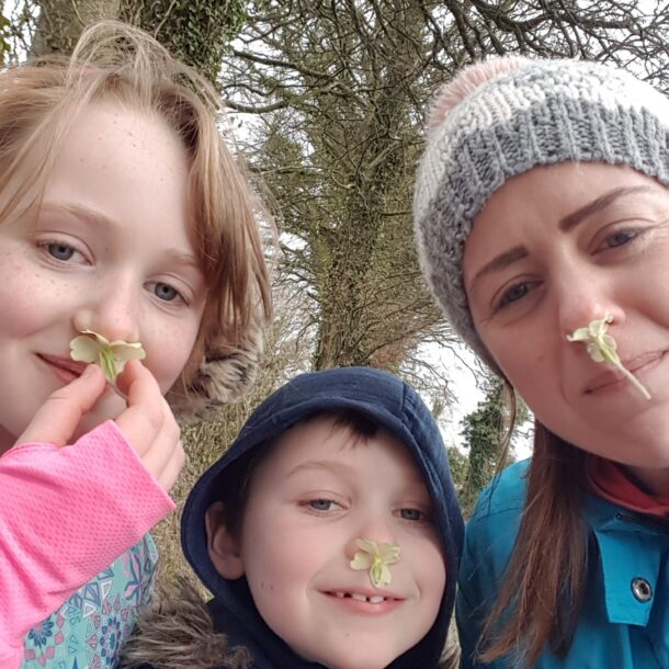 Leona Caoimhe and Caolán sniffing flowers on a daily walk